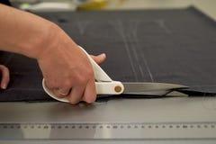 Meister schneidet Gewebe verschachtelung Das Entsprechen des Gewebes markierte mit weißer Kreide Schnitt und Nähen stockfoto