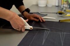 Meister schneidet Gewebe verschachtelung Das Entsprechen des Gewebes markierte mit weißer Kreide Schnitt und Nähen lizenzfreies stockfoto