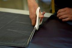 Meister schneidet Gewebe verschachtelung Das Entsprechen des Gewebes markierte mit weißer Kreide Schnitt und Nähen lizenzfreie stockbilder