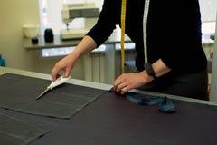 Meister schneidet Gewebe verschachtelung Das Entsprechen des Gewebes markierte mit weißer Kreide Schnitt und Nähen lizenzfreies stockbild