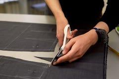 Meister schneidet Gewebe verschachtelung Das Entsprechen des Gewebes markierte mit weißer Kreide Schnitt und Nähen lizenzfreie stockfotos