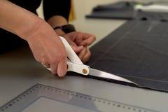 Meister schneidet Gewebe verschachtelung Das Entsprechen des Gewebes markierte mit weißer Kreide Schnitt und Nähen stockbild