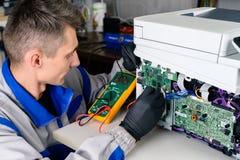 Meister sucht nach Schaden, ReparaturBüroeinrichtung unter Verwendung des Vielfachmessgeräts lizenzfreie stockfotografie