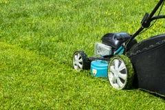 Meja gräsmattagräsklipparen på utrustning för gräs för gräsklippningsmaskin för grönt gräs som mejar dag för övre sikt för slut f Arkivfoto