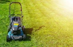 Meja gräsmattor, gräsklippare på grönt gräs, gräsklippningsmaskingräsutrustning som mejar hjälpmedlet för trädgårdsmästareomsorga fotografering för bildbyråer