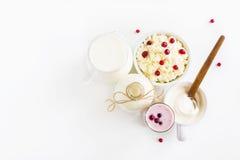Mejerijordbruksprodukter Mjölka i flaska, keso i bunke, kefir i krus, tranbäryoghurt i exponeringsglas, smör och nya bär Arkivfoton