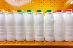 Mejeriproduktflaskor med ljusa räkningar på en hylla i shoppa arkivfoton