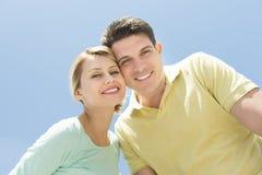 Mejilla derecha de los pares cariñosos a la mejilla contra el cielo azul claro fotografía de archivo libre de regalías