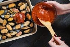 Mejillones crudos con la pasta de tomate en el fondo negro, cocinando foto de archivo