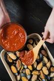 Mejillones crudos con la pasta de tomate en el fondo negro, cocinando imágenes de archivo libres de regalías