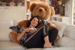Mejor mujer hermosa de la edad que miente en el sofá que se relaja, con un oso de peluche enorme fotos de archivo
