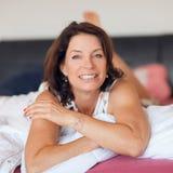 Mejor mujer hermosa de la edad que miente en la relajación de la cama, disfrutando de vida imagenes de archivo