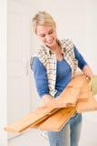 Mejoras para el hogar - handywoman lleve el tablón de madera foto de archivo libre de regalías