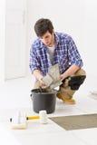 Mejoras para el hogar - manitas que pone el azulejo imagenes de archivo