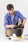 Mejoras para el hogar - manitas que pone el azulejo Imágenes de archivo libres de regalías