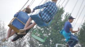 Mejores amigos adolescentes felices que montan el carrusel del chairoplane y que se divierten en el funfair metrajes
