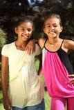Mejores amigos alegres de las muchachas que se colocan en el parque Foto de archivo