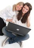 Mejores amigos con el ordenador portátil Fotos de archivo libres de regalías