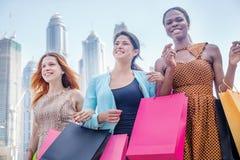 Mejores amigos de las compras Muchacha hermosa en el vestido que celebra compras Imagen de archivo