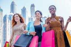 Mejores amigos de las compras Muchacha hermosa en el vestido que celebra compras Fotografía de archivo