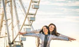 Mejores amigos de las mujeres jovenes que disfrutan del tiempo junto al aire libre en la rueda del transbordador imagen de archivo