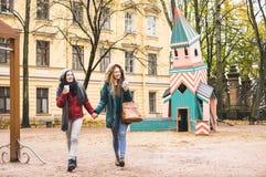 Mejores amigos de las mujeres jovenes que disfrutan invierno junto al aire libre Foto de archivo