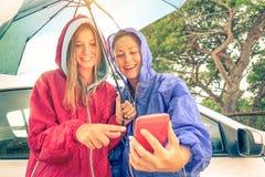 Mejores amigos de las mujeres que gozan con smartphone con el sol que sale Fotos de archivo libres de regalías