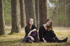 Mejores amigos de los adolescentes que se sientan en la naturaleza del bosque Imagen de archivo libre de regalías