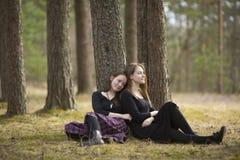 Mejores amigos de los adolescentes que se sientan en la naturaleza del bosque Fotos de archivo libres de regalías