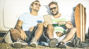 Mejores amigos del inconformista que se divierten con la tableta en el momento del viaje del coche Fotos de archivo