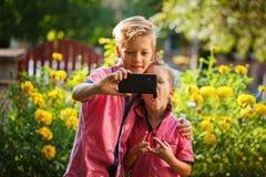 Mejores amigos Dos niños pequeños lindos que hacen el selfie y que hacen caras divertidas al aire libre Foco suave en el teléfono Foto de archivo libre de regalías