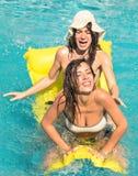 Mejores amigos en bikini que disfrutan del tiempo junto en piscina Imagen de archivo