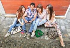 Mejores amigos multirraciales felices que se divierten usando el teléfono elegante móvil Imagen de archivo libre de regalías