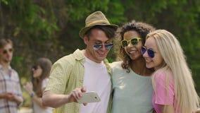 Mejores amigos que bailan y que toman el selfie en el festival al aire libre del verano fresco, juventud metrajes