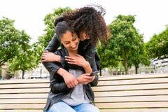 Mejores amigos que charlan con smartphone en banco de parque Foto de archivo