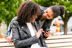 Mejores amigos que charlan con smartphone en banco de parque Imagen de archivo