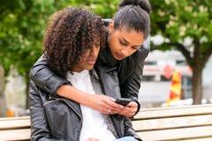Mejores amigos que charlan con smartphone en banco de parque Foto de archivo libre de regalías