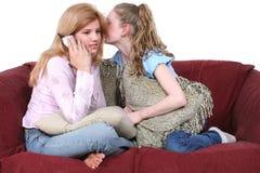 Mejores amigos que chismean en el teléfono que se sienta en el sofá Foto de archivo