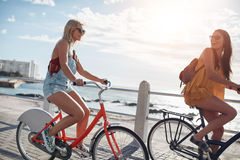 Mejores amigos que completan un ciclo a lo largo de la 'promenade' de la playa Foto de archivo