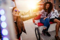 Mejores amigos que disfrutan de paseo del triciclo en la ciudad Imágenes de archivo libres de regalías