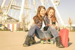 Mejores amigos que disfrutan de tiempo así como smartphone y música Fotografía de archivo libre de regalías