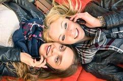 Mejores amigos que disfrutan del tiempo junto al aire libre con smartphone Fotos de archivo libres de regalías