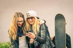 Mejores amigos que disfrutan del tiempo junto al aire libre con smartphone Fotos de archivo