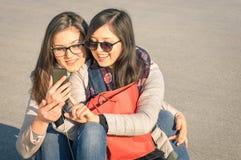 Mejores amigos que gozan de novias del tiempo juntas - con smartphone Foto de archivo libre de regalías