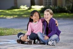 Mejores amigos que juegan junto en la calzada Foto de archivo libre de regalías