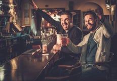 Mejores amigos que se divierten que mira un partido de fútbol en la TV y que bebe la cerveza de barril en el contador de la barra foto de archivo