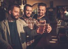 Mejores amigos que se divierten y que beben la cerveza de barril en el contador de la barra en pub imágenes de archivo libres de regalías