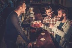 Mejores amigos que se divierten y que beben la cerveza de barril en el contador de la barra en pub imagen de archivo libre de regalías