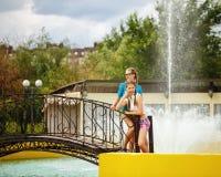 Mejores amigos que se relajan en un puente cerca de la fuente Foto de archivo libre de regalías