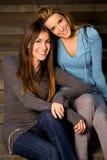 Mejores amigos que se sientan en pasos de progresión Fotos de archivo libres de regalías